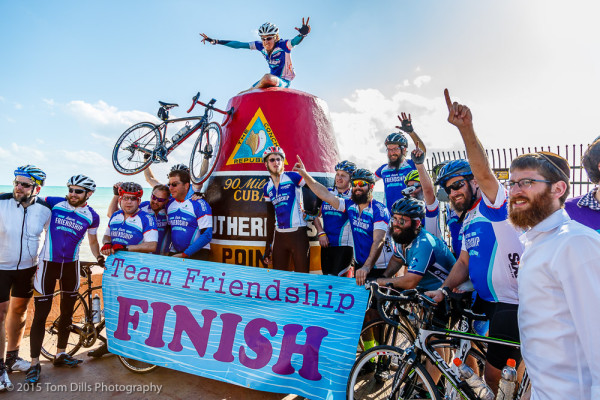 A group of bicyclists celebrate at the Southernmost Point marker after riding from Miami
